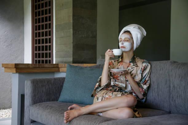 Junge Frau sitzt zu Hause mit Gesicht Schönheit Maske, während eine Tasse Kaffee. Gemütliche Zeit zu Hause. Selbstzeit und Home-Spa-Konzept. Coronavirus-Ausbruch und Selbstquarantäne-Konzept. – Foto