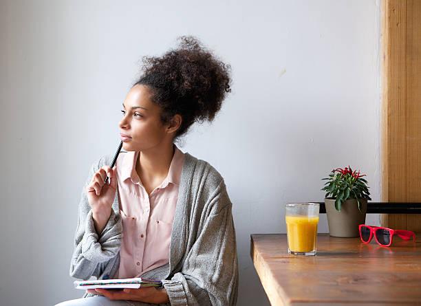 Jovem mulher sentada em casa com papel e caneta - foto de acervo