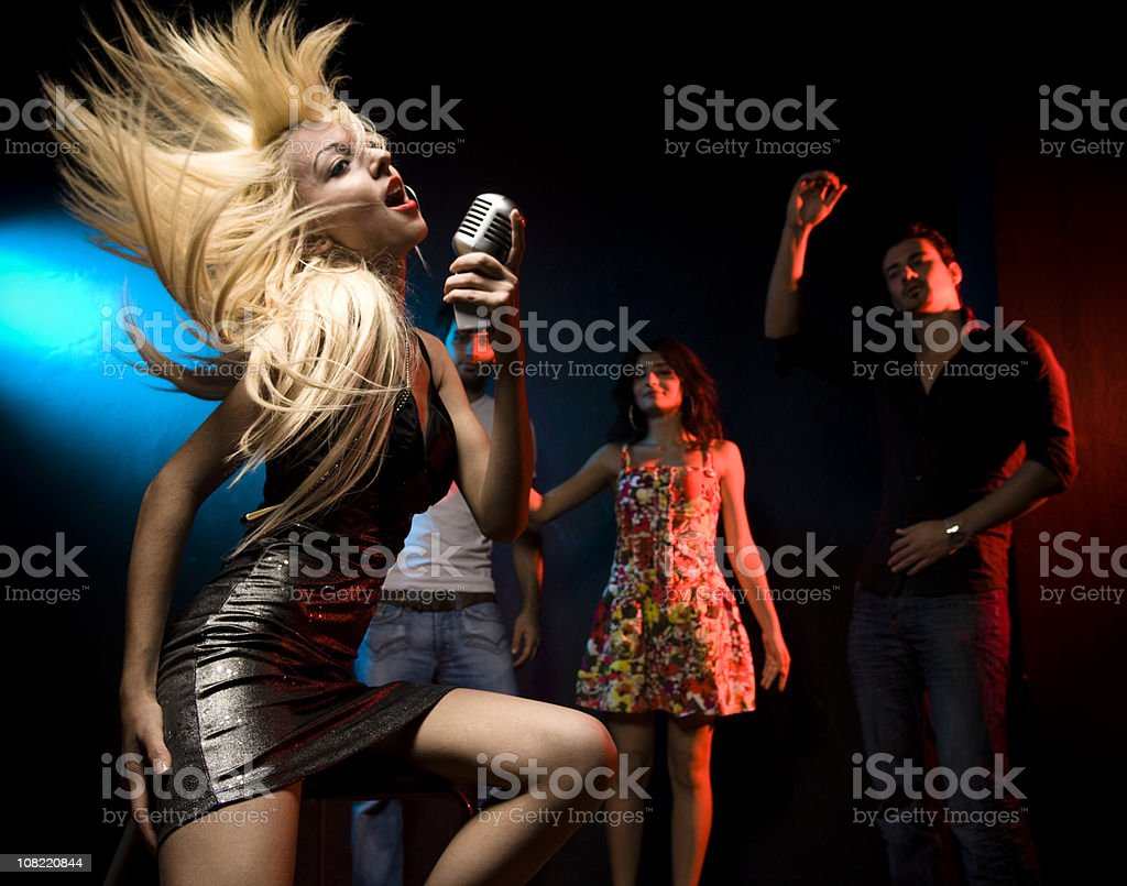 Young Woman Sitting at Singing for Crowd in Nightclub royalty-free stock photo