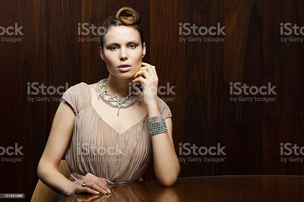Young woman sitting at table, portrait stock photo
