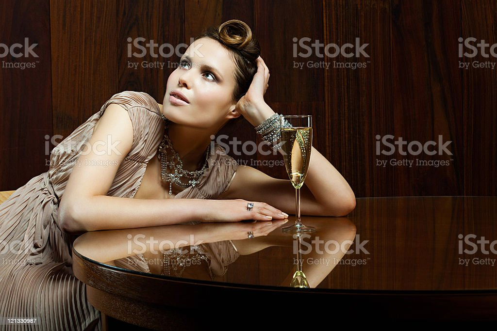 Young woman sitting at table with champagne stock photo