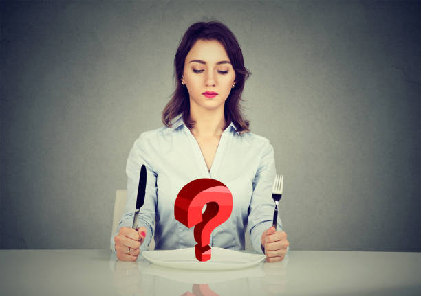 young woman sitting at table with fork and knife looking at plate with red  question mark isolated on gray background - serving size stock photos and pictures
