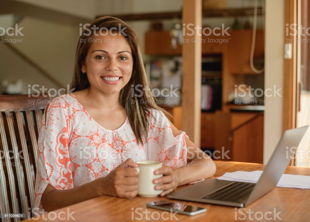 Young woman sitting at table with laptop and coffee stock photo