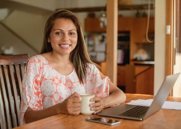 young woman sitting at table with laptop and coffee - pacific islander ethnicity stock photos and pictures