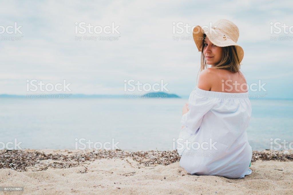 foto de jovem mulher sentados a bech e aproveitando o dia ensolarado