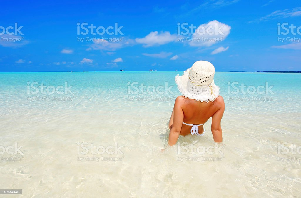 Young woman sitting at the sea shore. royalty free stockfoto