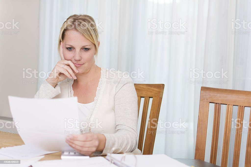 A young woman sitting at the table reading a letter stock photo