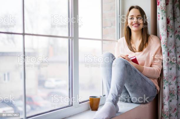 Young woman sitting at window drinking coffee and reading a book picture id851862962?b=1&k=6&m=851862962&s=612x612&h=lwiwe7q1fqd8svvlovosmx6z9u8edjl jdimwjkz9so=