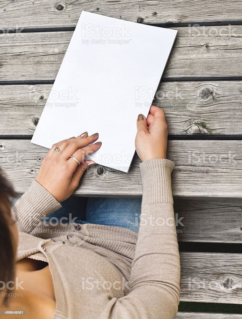 Young woman sitting at wooden table with a booklet stock photo