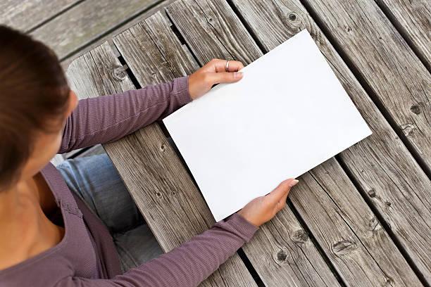 Junge Frau sitzen am Holztisch mit einem booklet – Foto