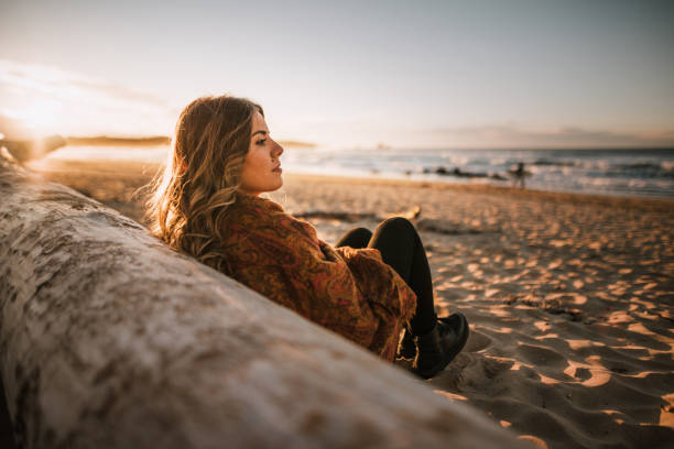 Young woman sitting by a beach at sunset in winter stock photo