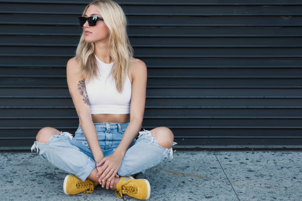 junge Frau sitzt an einer schwarzen Wand mit Sonnenbrille – Foto