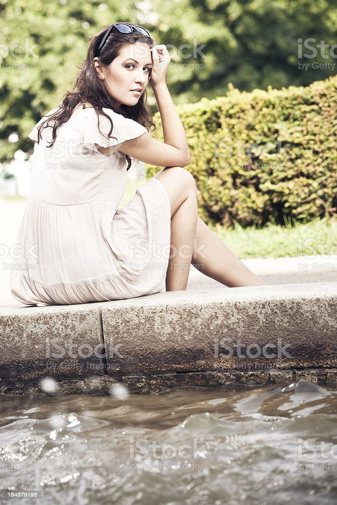 young woman sitting by a fountain stock photo