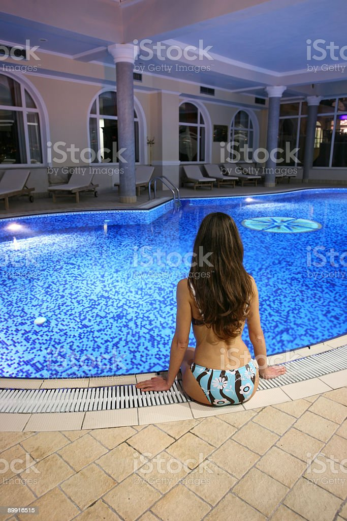 Young woman sitting by the pool royalty-free stock photo