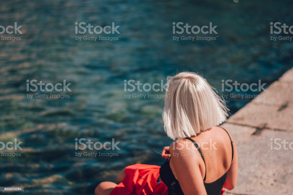 Young woman sitting by the sea stock photo