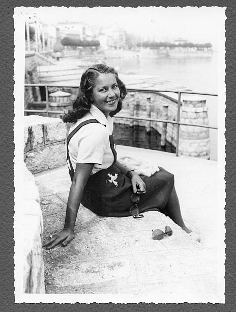 young woman sitting by the sea,1940.black and white. - 1940s style stock photos and pictures