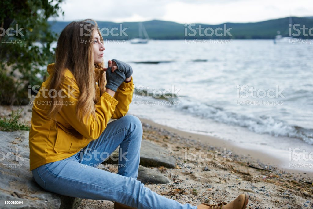 Young woman sitting by the shore stock photo