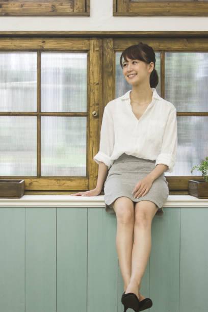 窓際に座って笑っている若い女性。 ストックフォト