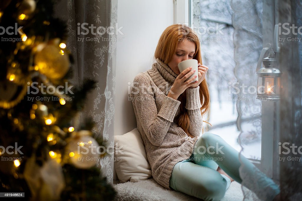 Young woman sitting by the window drinking hot coffee royalty-free stock photo
