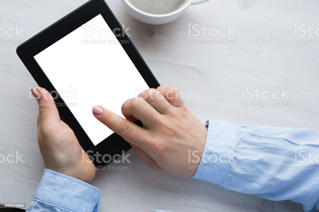 Young woman sitting by the window with an e-book stock photo