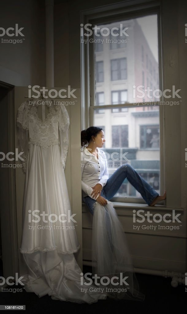 Young Woman Sitting by Window with Wedding Dress Hanging Near royalty-free stock photo