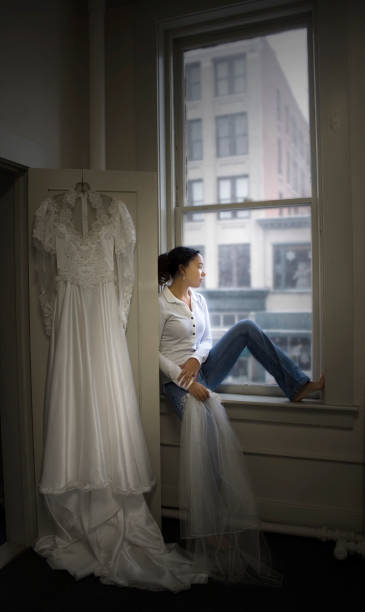 Young Woman Sitting By Window With Wedding Dress Hanging Near Stock Photo
