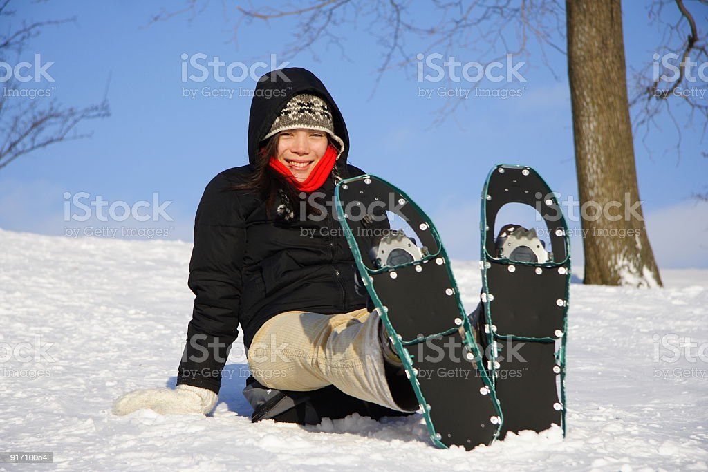 Young woman sitting down with snowshoes stock photo