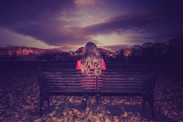 Young woman sitting facing away on a park bench stock photo