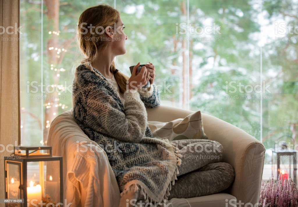 Young woman sitting home by the window stock photo