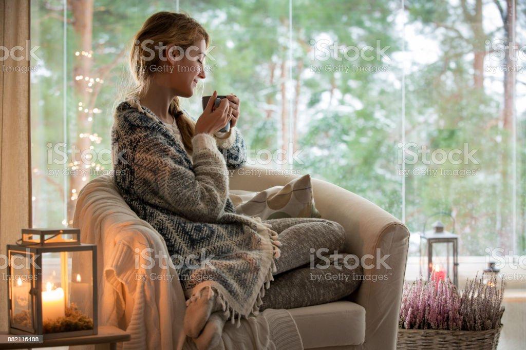 Ung kvinna sitta hem genom fönstret - Royaltyfri Avkoppling Bildbanksbilder