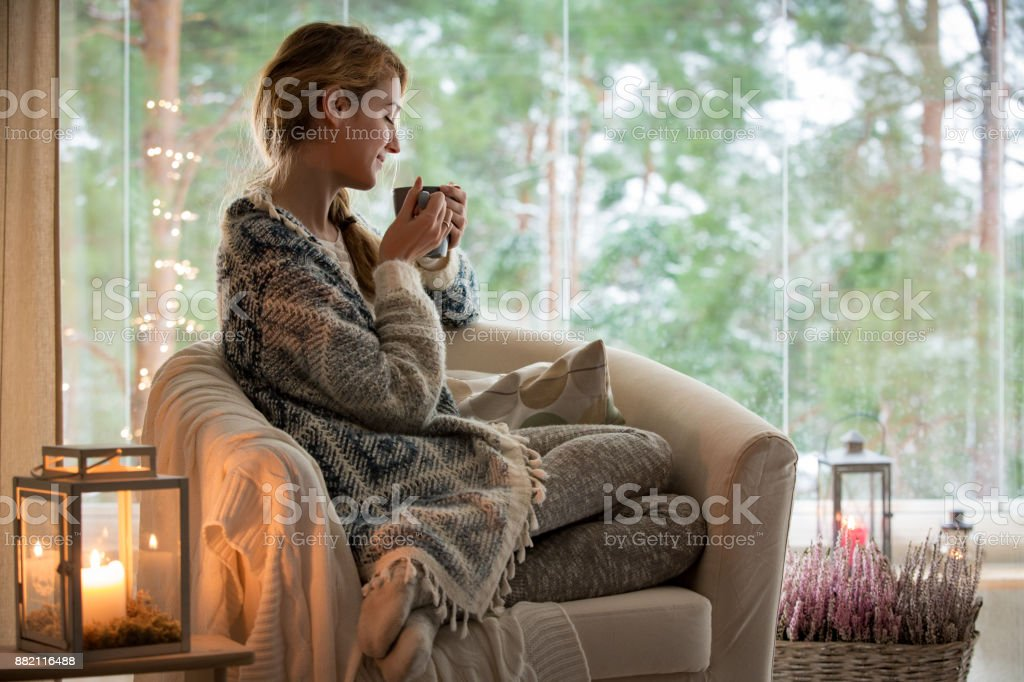 Young woman sitting home by the window