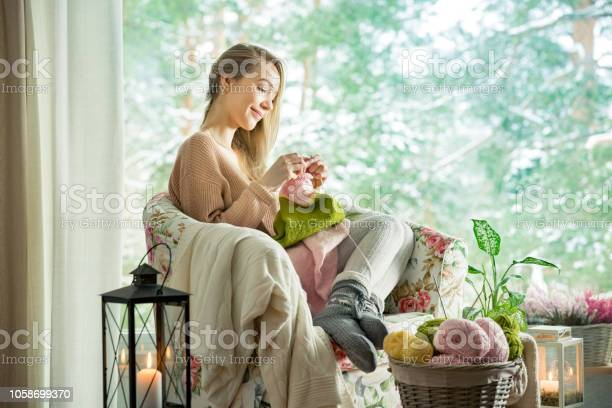 Young woman sitting home in a chair by the window wearing knitted picture id1058699370?b=1&k=6&m=1058699370&s=612x612&h= mhfz1uhhgjh88dlyalgjfaklajmhu9twu9wegamvnq=