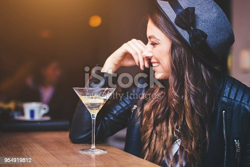 Young brunette woman sitting at a bar and enjoying a cocktail with a lemon twist.