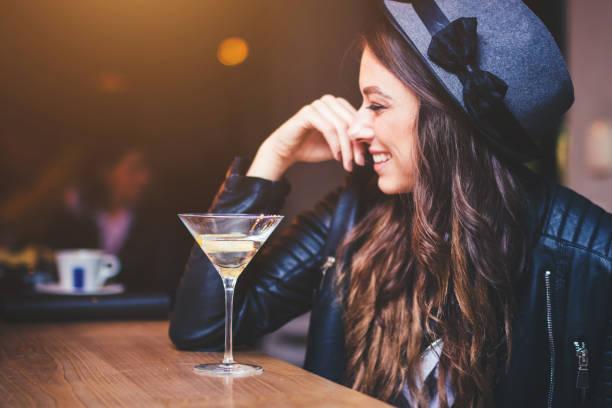 junge frau sitzt in einer bar - cocktails mit wodka stock-fotos und bilder