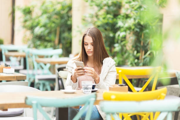 Young woman sitting in a cafe outdoors and using smart phone stock photo