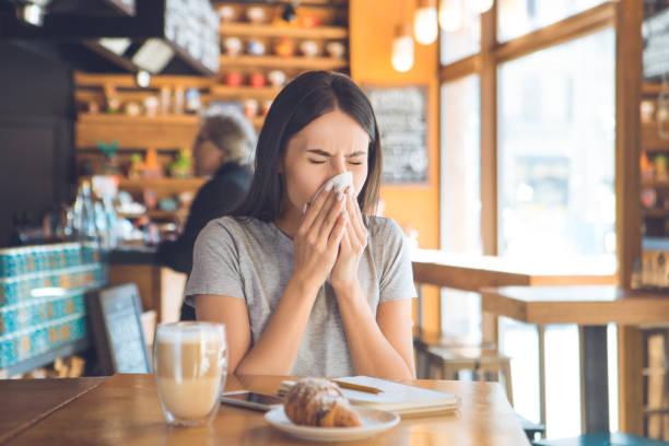 junge frau sitzt in einem coffee-shop-freizeit - schnäuzen stock-fotos und bilder