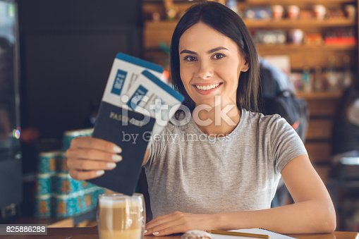 Young female sitting in a cafe indoors rest holding tickets