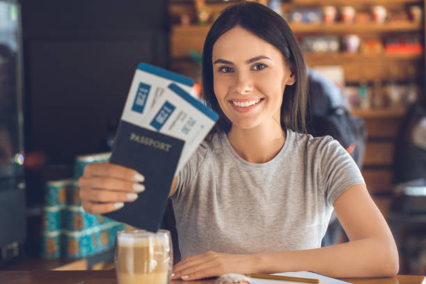 young woman sitting in a coffee shop leisure - aeroplane ticket stock photos and pictures