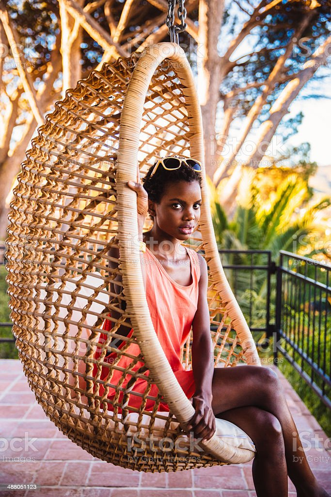 Young woman sitting in a hanging chair stock photo