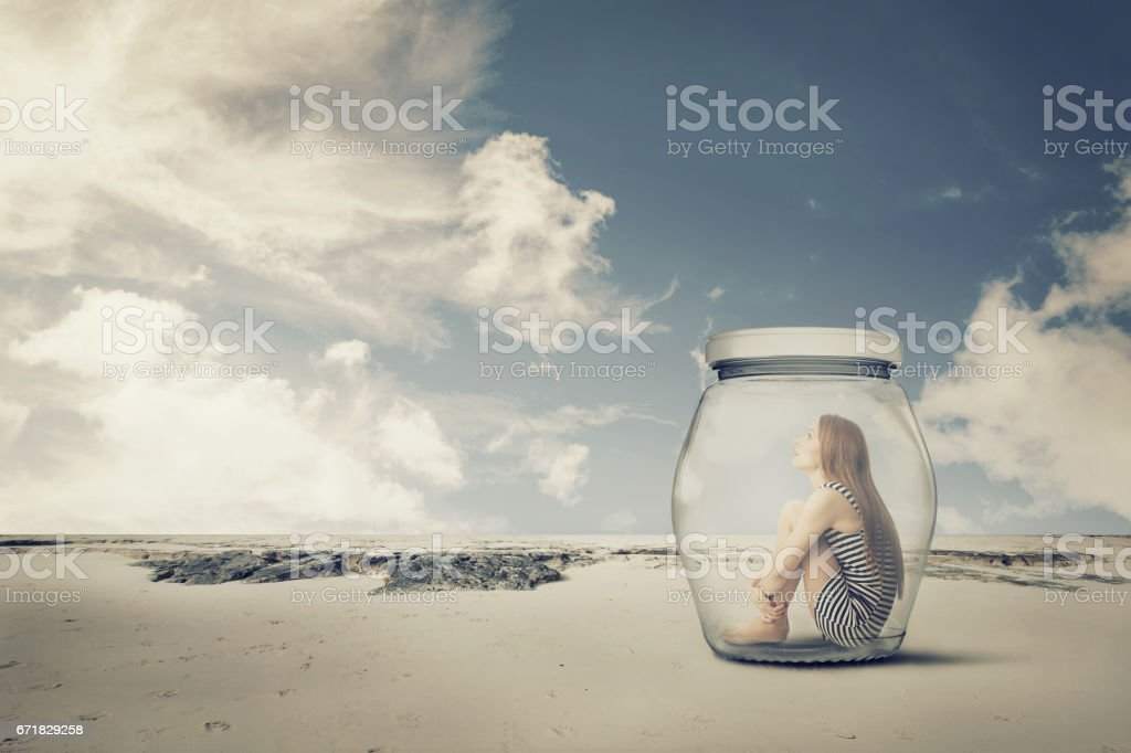 young woman sitting in a jar in the desert. Loneliness outlier concept stock photo