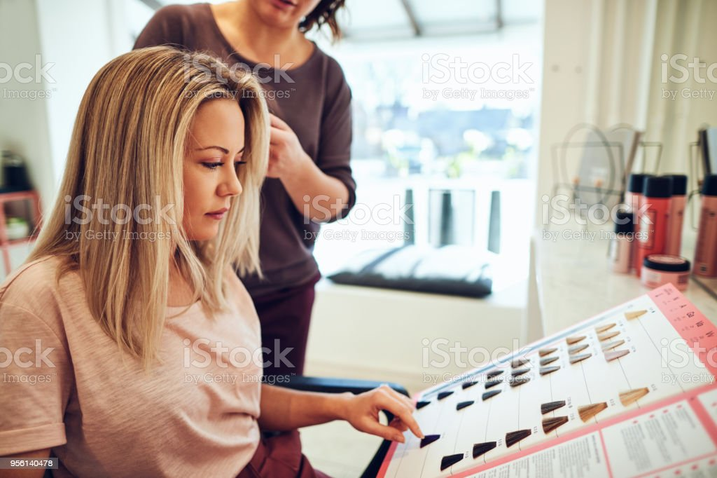 Young Woman Sitting In A Salon Chair Choosing Hair Dye Stock Photo