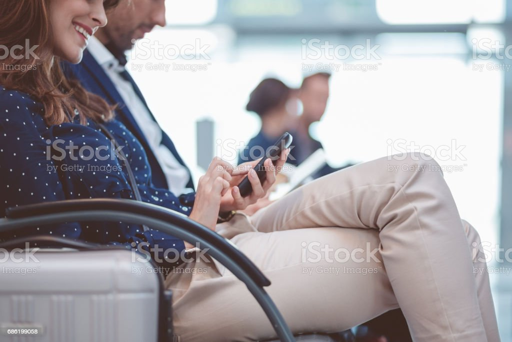 Young woman sitting in airport lounge using mobile phone stock photo