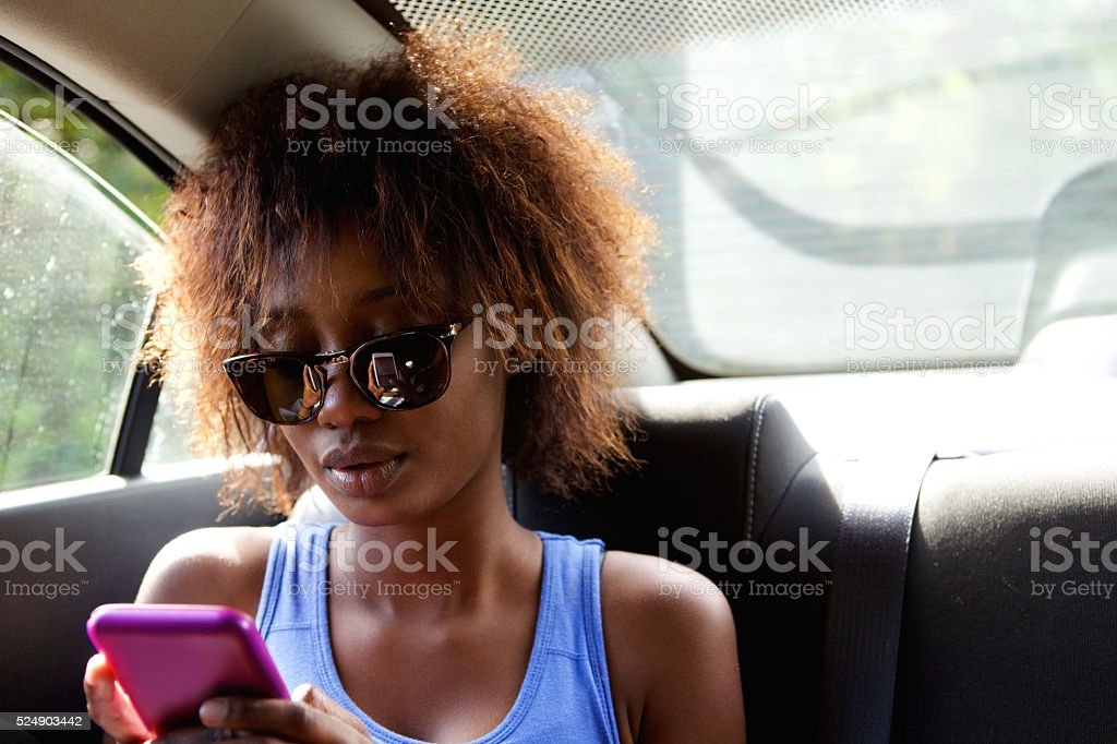 Young woman sitting in backseat of car with cell phone stock photo
