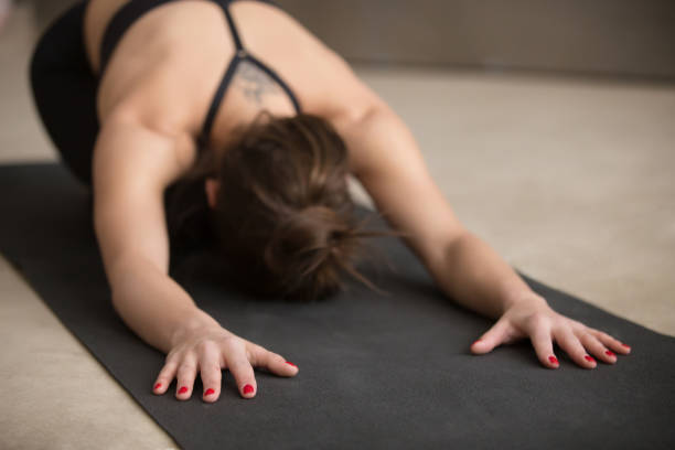 Young woman sitting in Balasana pose, grey studio background, cl Young attractive woman practicing yoga, stretching in Child exercise, Balasana pose, working out, wearing black sportswear, urban style grey studio floor, close up, focus on fingers shoulder stand stock pictures, royalty-free photos & images