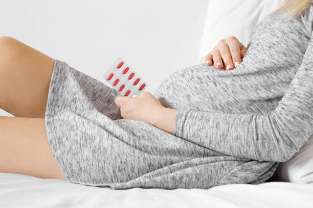 young woman sitting in bed and holding blister pack of red pills for improve of iron level in blood. receiving vitamins in pregnancy time. side view. - anemia foto e immagini stock