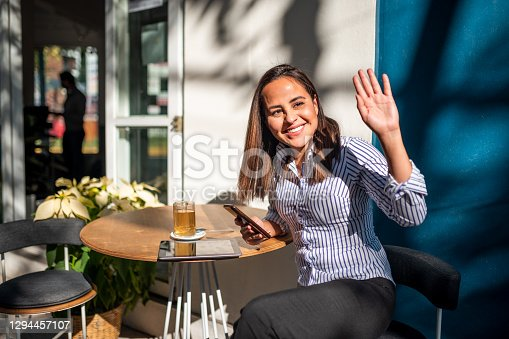 Young woman sitting at cafe and using digital tablet