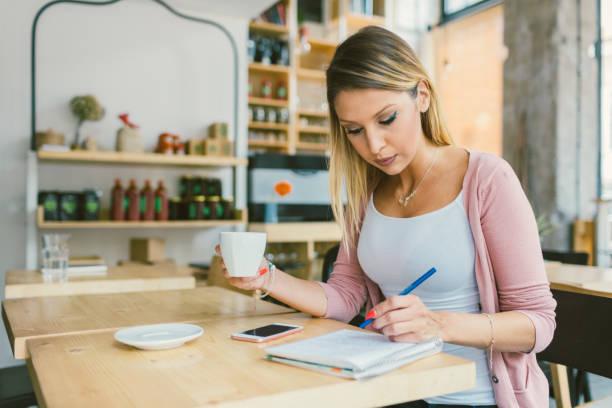 jeune femme, assis dans le café et l'écriture - gaucher photos et images de collection