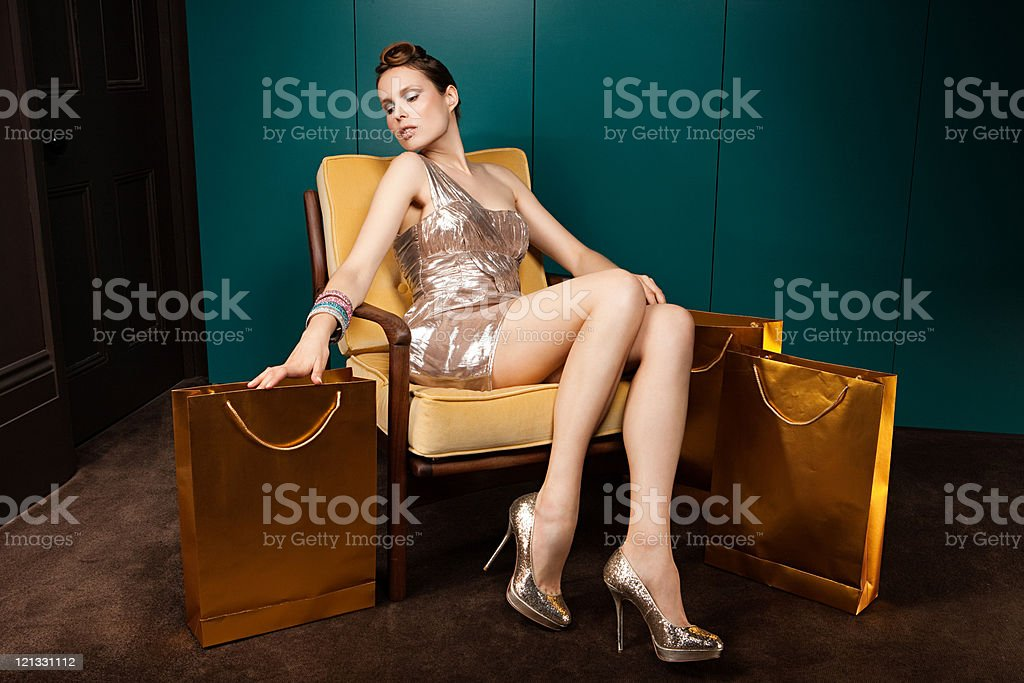 Young woman sitting in chair with shopping bags stock photo