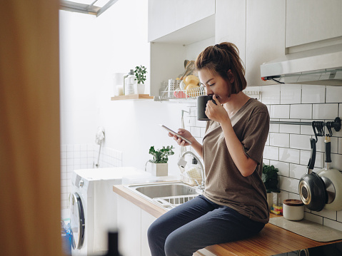 Teenage asian woman drinking coffee while sitting on kitchen counter and working on smart phone in morning at home.