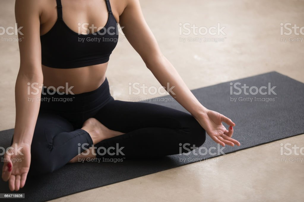 Young woman sitting in Easy Seat pose with mudra, studio stock photo